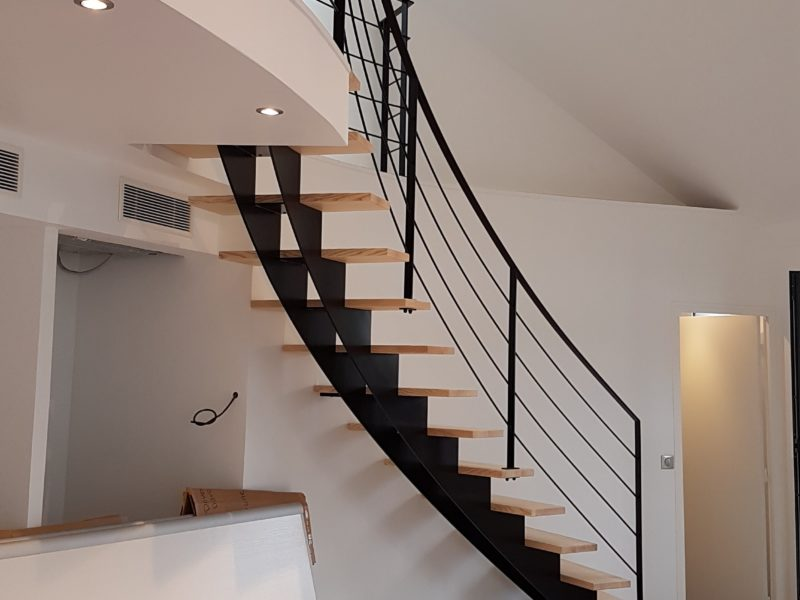 Escalier métallique courbe à claire voie , marches en bois. Main courante acier laqué Réalisation Artis architectes associés